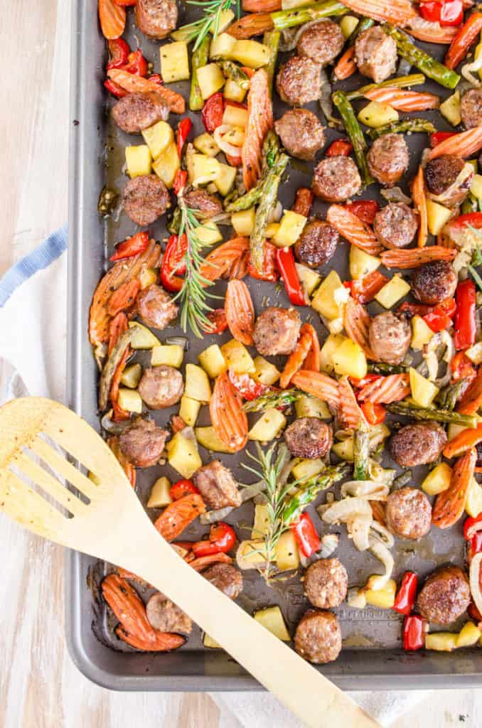 A pic looking strait down on a fully roasted 30 Minute Italian Sausage Sheet Pan Dinner garnished with fresh sprigs of rosemary - The Goldilocks Kitchen