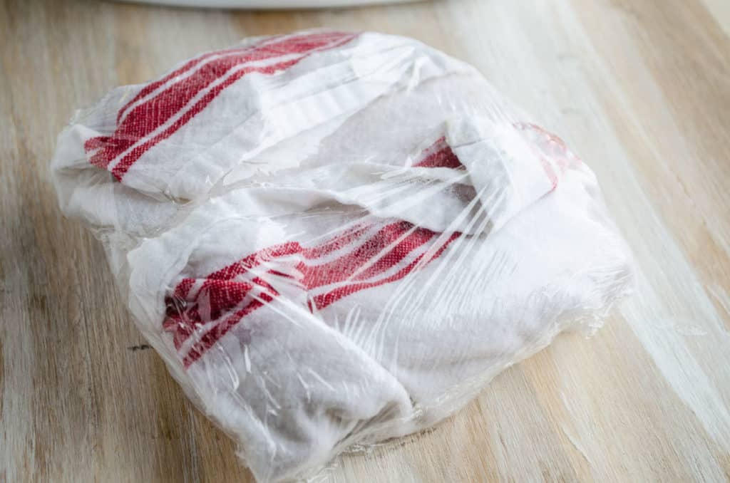 Corn Tortillas are wrapped in a wet dish towel, which is wrapped in plastic wrap to steam them for Black Bean Sweet Potato Enchiladas - The Goldilocks Kitchen
