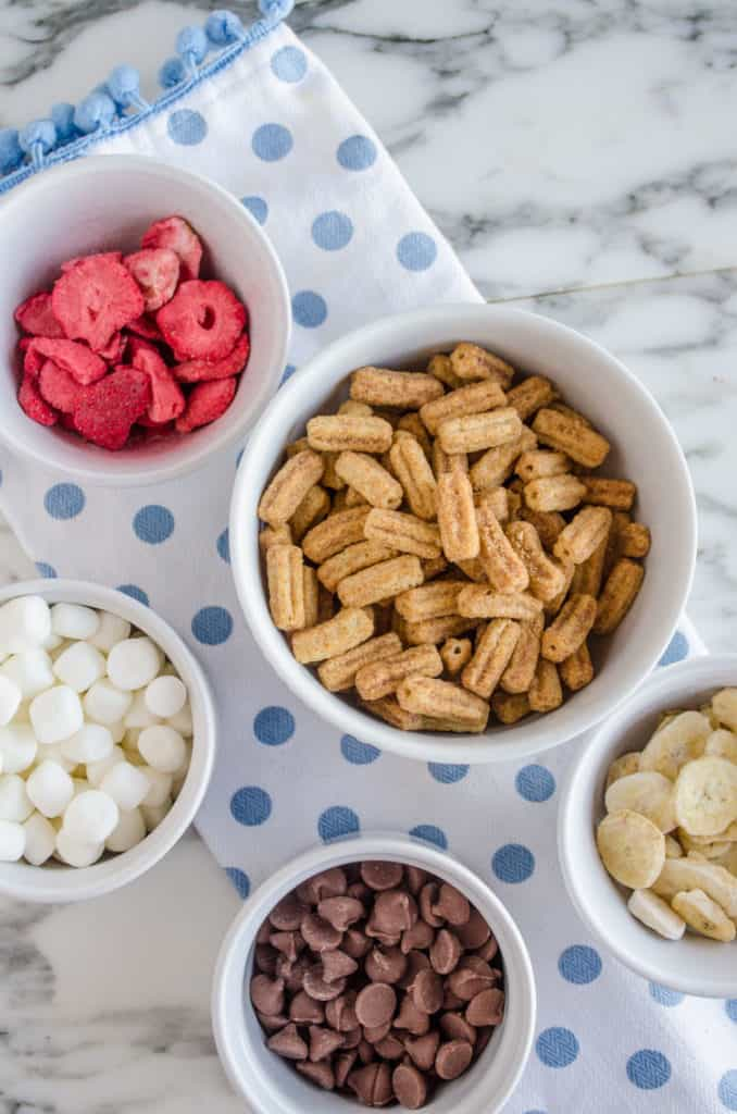 Looking down into white bowls containing dried strawberries, marshmallows, chocolate chips, Cinnamon Toast Crunch Churros Cereal, and dried banana chips for making Churros Snack Mix - The Goldilocks Kitchen