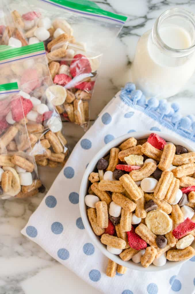 A close up of a bowl of Churros Snack Mix along with baggies filled with Churros Snack Mix - The Goldilocks Kitchen