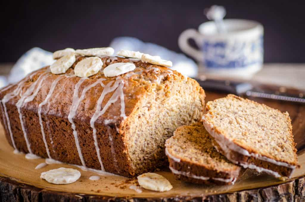A Orange Spice Banana Bread loaf drizzled with glaze has a few slices sitting next to the loaf - The Goldilocks Kitchen