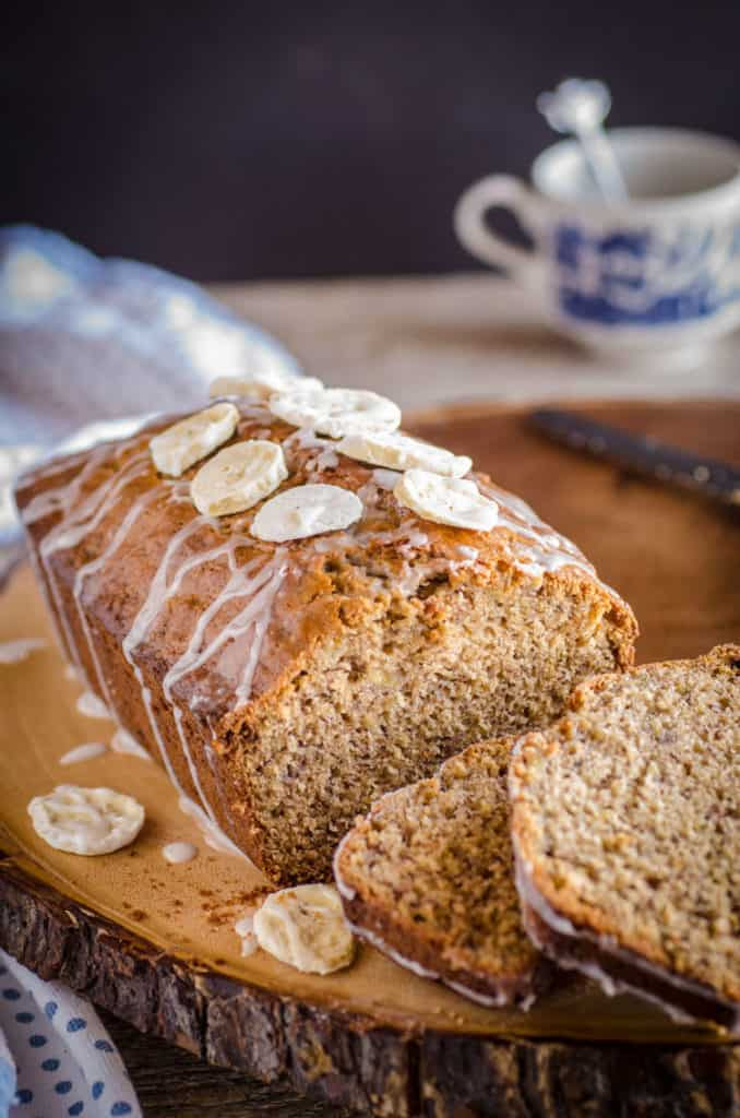 A loaf of Orange Spice Banana Bread with a few slices sitting on the end and a teacup in the background - The Goldilocks Kitchen