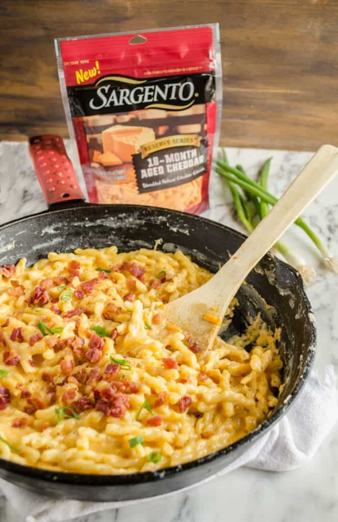 A closeup picture of a bag of Sargento Reserve Series 18-Month Aged Cheddar and a few green scallions, beside a cast iron skillet with One-Skillet Bacon Mac and Cheese in it. - The Goldilocks Kitchen