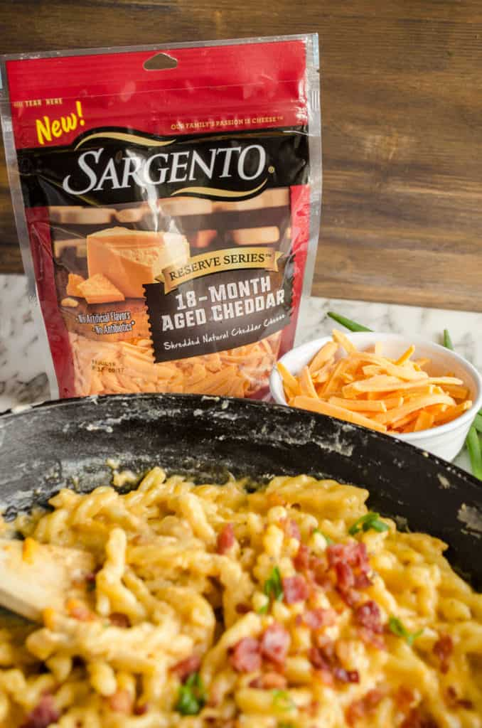A closeup picture of a bag of Sargento Reserve Series 18-Month Aged Cheddar, beside a bowl of shredded cheddar and a cast iron skillet with One-Skillet Bacon Mac and Cheese in it. - The Goldilocks Kitchen