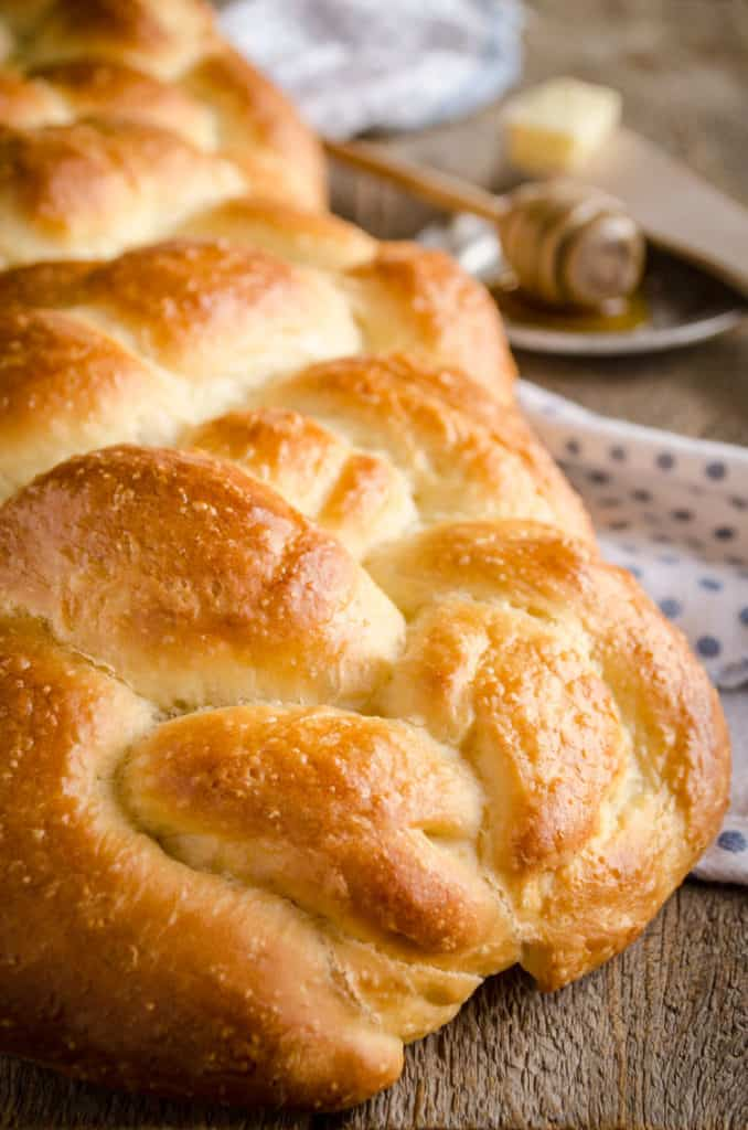 A closeup of freshly baked Braided Challah Bread on a wooden table with a honey wand and a pat of butter - The Goldilocks Kitchen