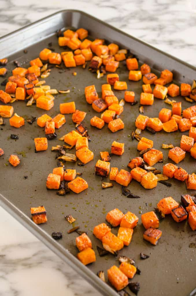 Cubed roasted butternut squash in a rimmed baking sheet used to make Grilled Chicken Tacos with Green Chile Cream Sauce - The Goldilocks Kitchen