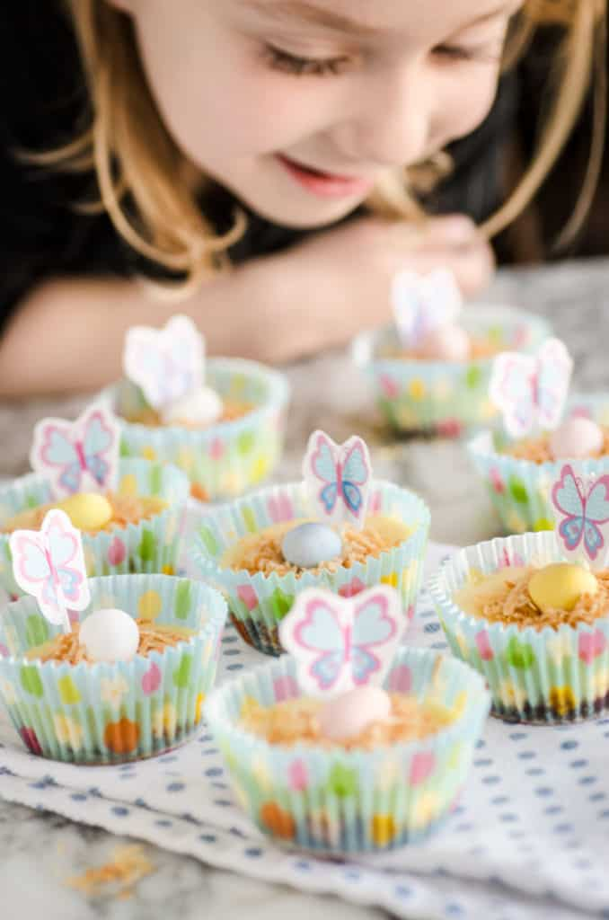 A young girl looks down on several Strawberry Mini-Cheesecakes decorated for Easter- The Goldilocks Kitchen