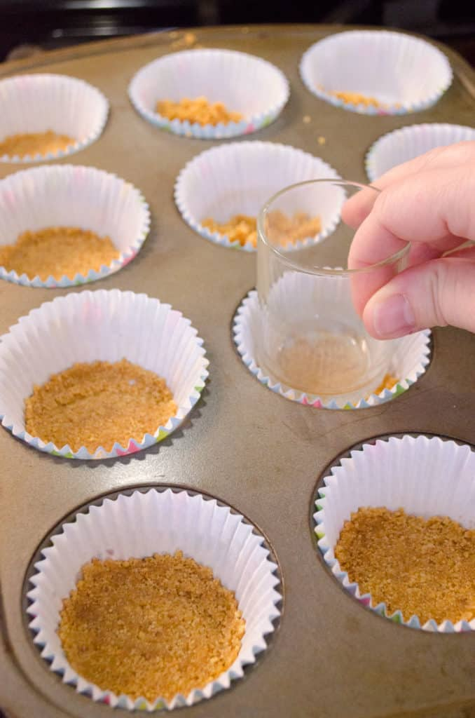 Graham cracker crust is pressed into the bottoms of cupcake liners placed into a muffin tin to make Strawberry Mini-Cheesecakes - The Goldilocks Kitchen