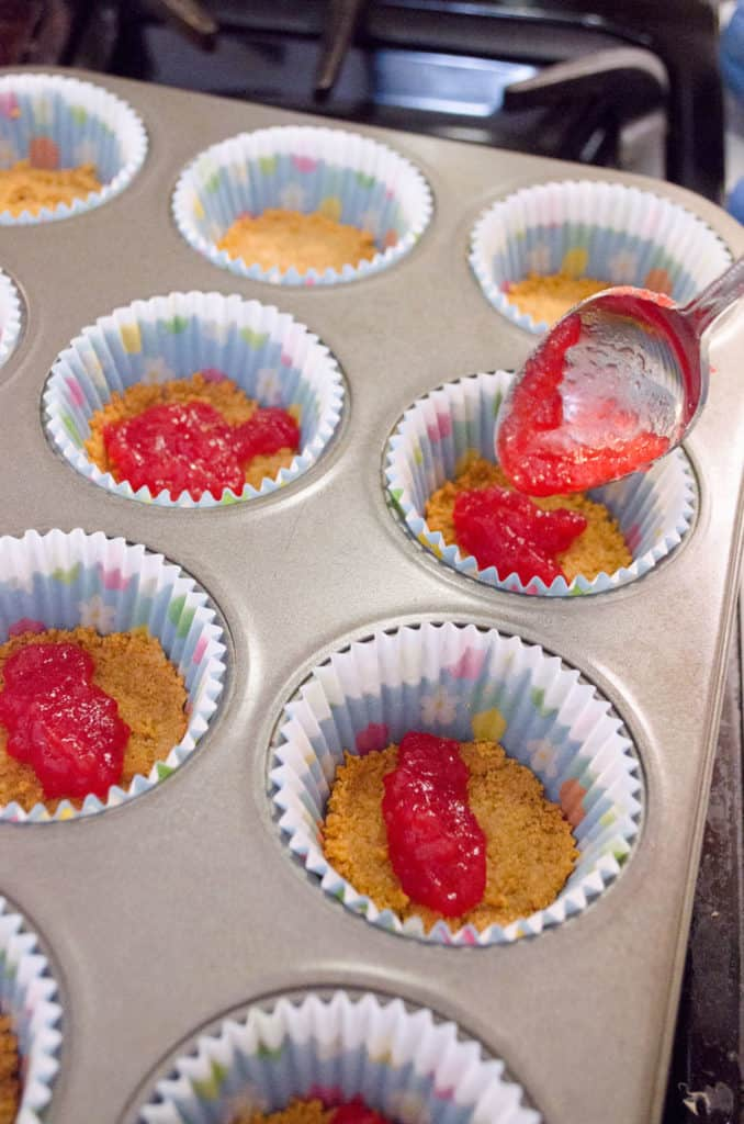 Spoon fulls of strawberry jam are placed into cupcake liners with graham cracker crust in the bottom to make Strawberry Mini-Cheesecakes - The Goldilocks Kitchen