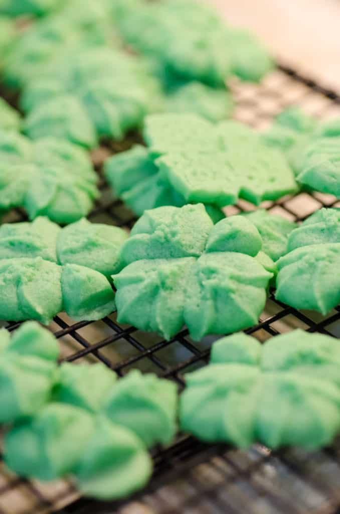 A close up picture of St. Patricks Day Cream Cheese Spritz Cookies cooling on a wire rack - The Goldilocks Kitchen