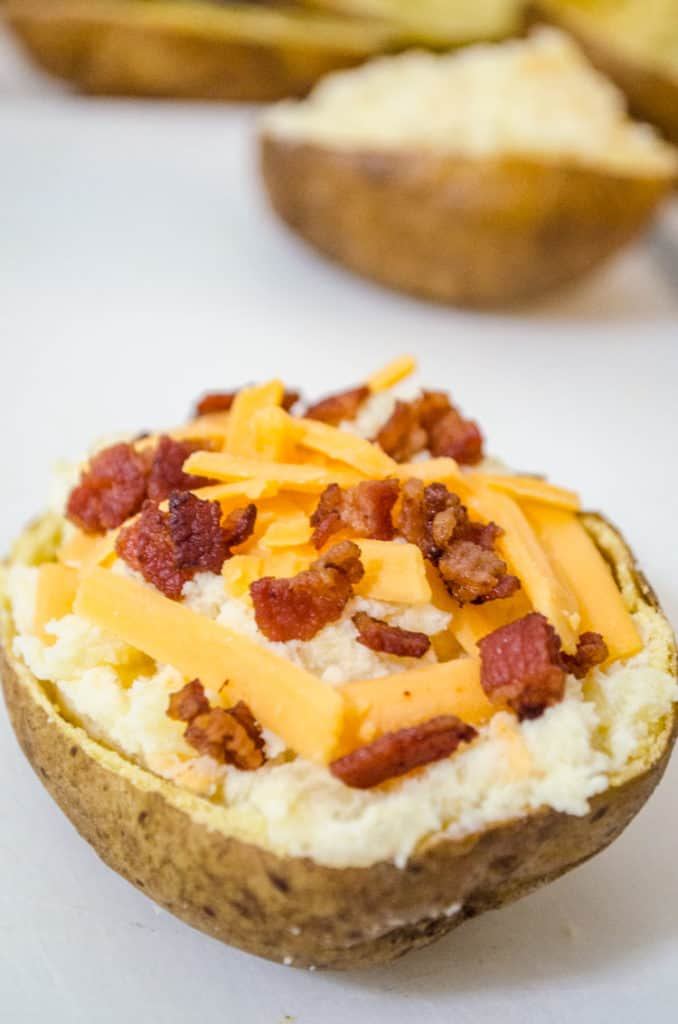 A close picture of a potato skin filled with potato filling, topped with shredded cheddar and bacon for Make Ahead Twice Baked Potatoes - The Goldilocks Kitchen