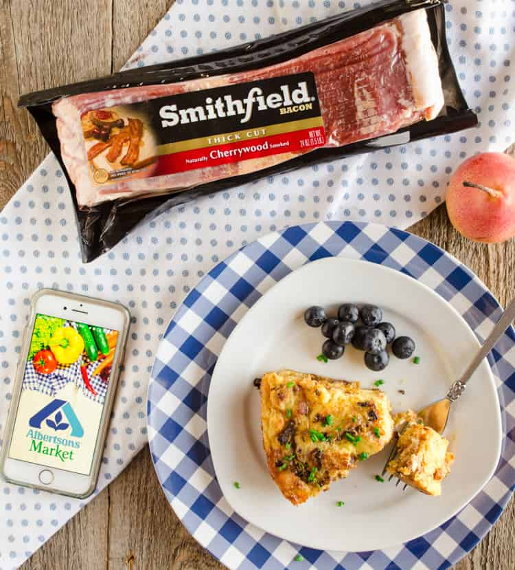Bacon Cheddar 30 Minute Skillet Strata slice on a plate next to a package of Smithfield Bacon and an iPhone with the Albertsons Market logo - The Goldilocks Kitchen
