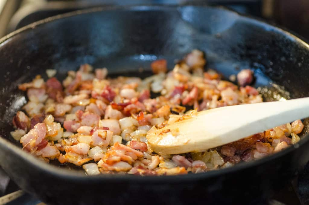 Chopped onion and bacon brown in a cast-iron skillet to make a Bacon Cheddar 30 Minute Skillet Strata - The Goldilocks Kitchen