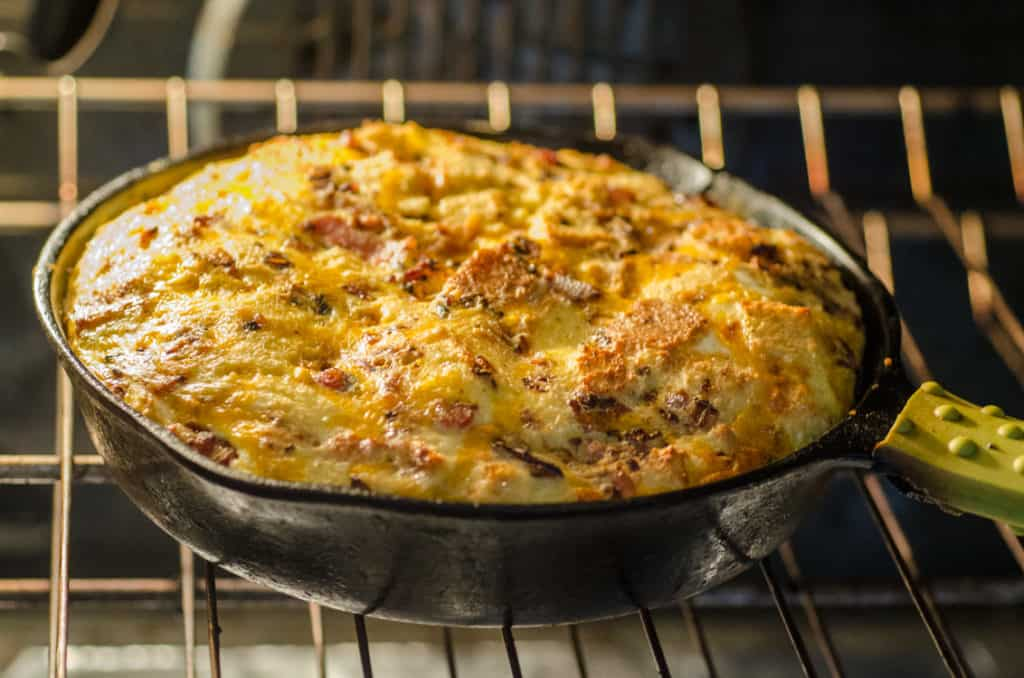 A puffed up Bacon Cheddar 30 Minute Skillet Strata bakes in a cast-iron skillet - The Goldilocks Kitchen