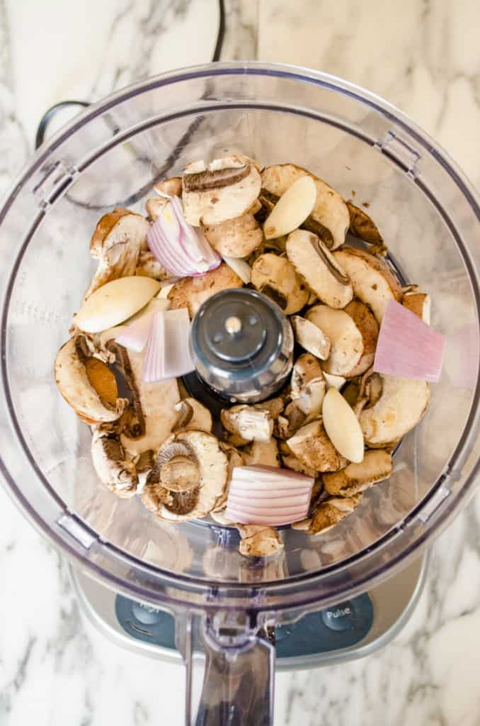 Looking down into a food processor containing sliced brown mushrooms, chunks of shallot and a few cloves of garlic to make Easy Meatball Wellingtons - The Goldilocks Kitchen