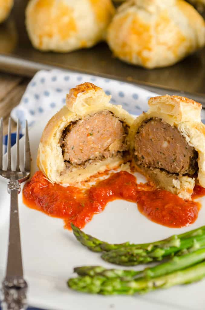 Easy Meatball Wellingtons made with Carando brand meatballs. One is sliced open on a plate showing the meatball center. - The Goldilocks Kitchen