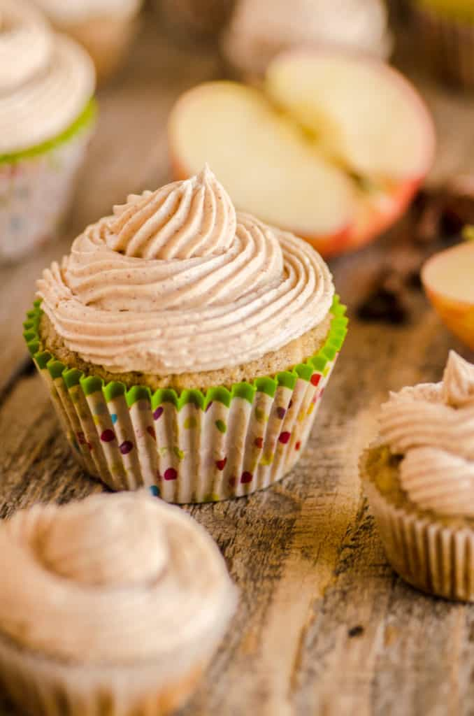 Apple Cinnamon Cupcakes with cinnamon buttercream frosting swirled on top are displayed on a wooden table with apple slice in the background- The Goldilocks Kitchen