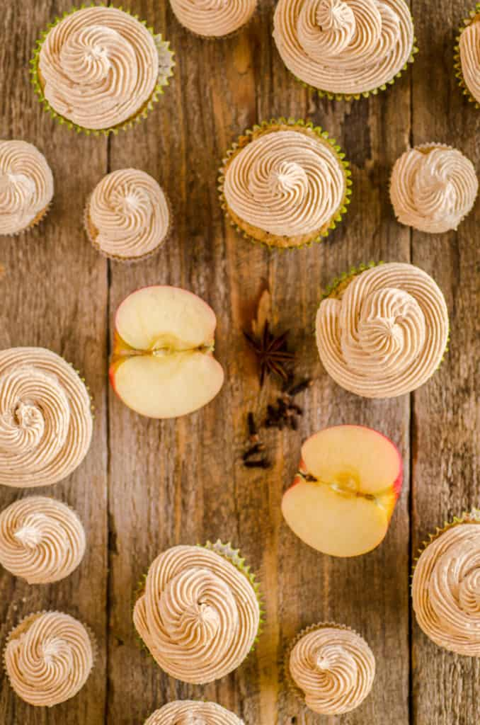 Apple Cinnamon Cupcakes from above on a wooden table; including regular sized and mini cupcakes, all with swirls of cinnamon buttercream frosting.- The Goldilocks Kitchen