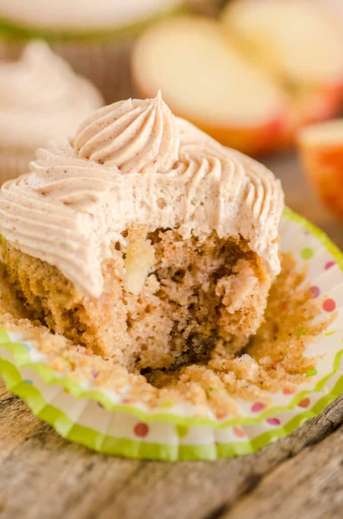 A closeup picture of a frosted cupcake with a bite out of the side showing the texture and apple pieces in the cake. Apple Cinnamon Cupcakes