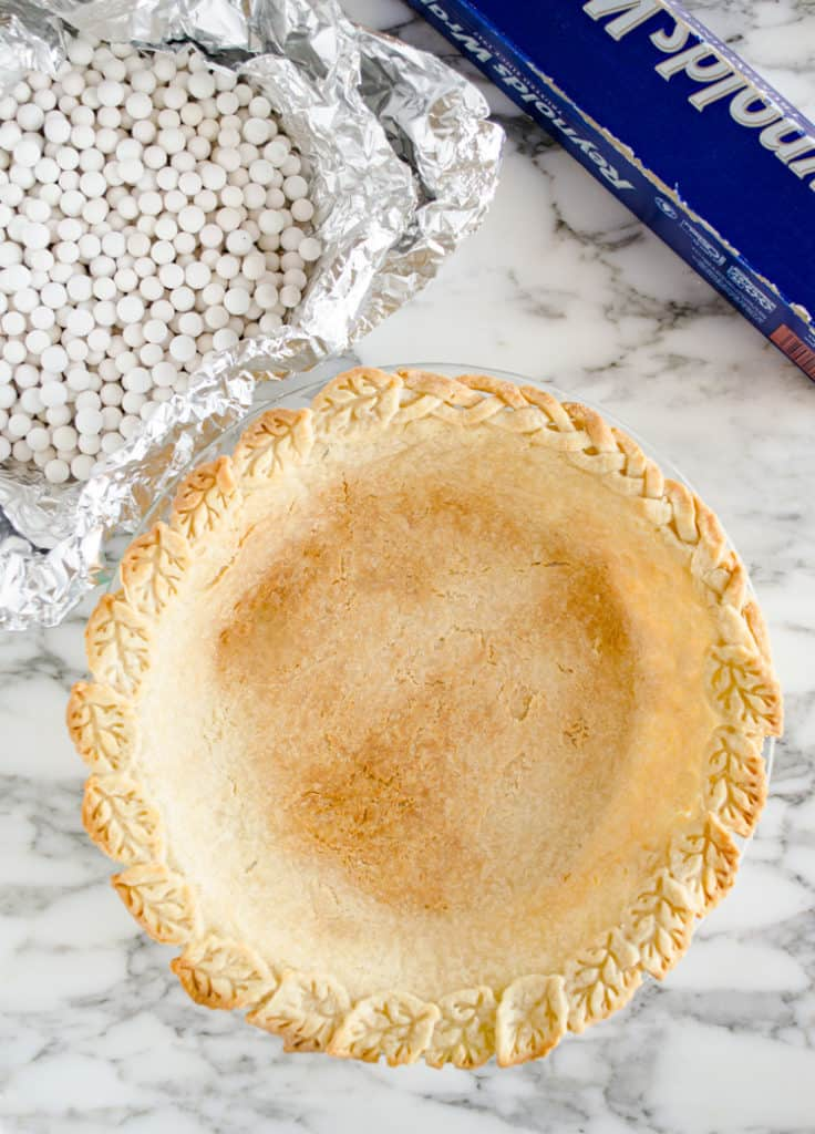 Pie weights and a box of aluminum foil sit next to a golden brown empty pie crust that is fully prebaked and ready for a fruit or custard filling - The Goldilocks Kitchen
