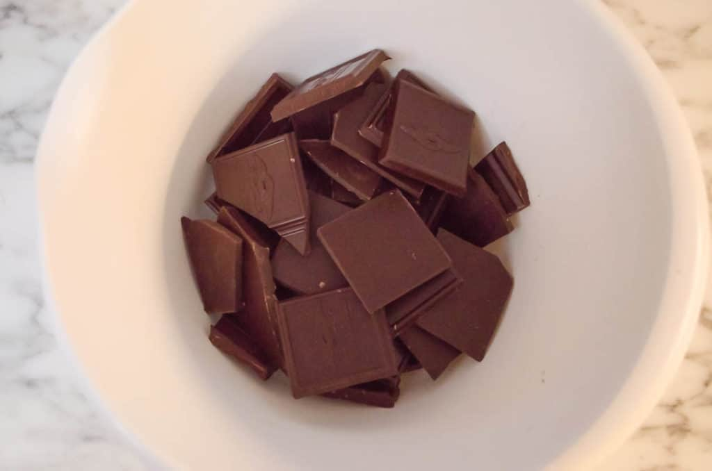 Ghiradeli chocolate squares sit broken at the bottom of a white mixing bowl so they can be melted to make French Silk Pie without Raw Eggs - The Goldilocks Kitchen