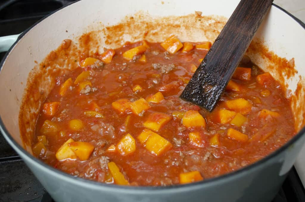 Green Chile Squash Goulash cooks in a stovetop Dutch oven.