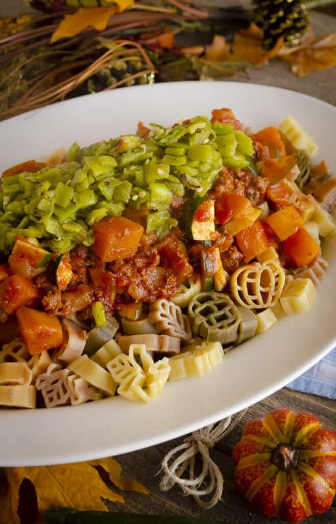 Green Chile Squash Goulash served over multi-colored pasta, piled into a large white oval platter.