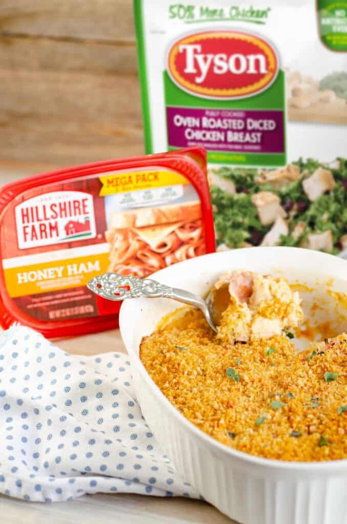 Packages of Tyson Oven Roasted Diced Chicken Breast and Hillshire Farm Honey Ham Lunch meat sit behind a white ceramic casserole dish filled with Easy Weeknight Chicken Cordon Bleu Casserole.