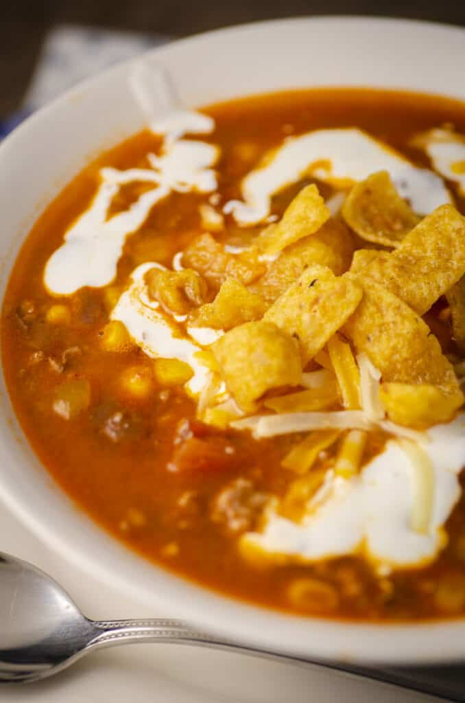An extreme closeup of a bowl of Weeknight Taco soup showing corn, beans, tomatoes and ground beef in broth. The bowl is garnished with sour cream, shredded cheese and tortilla strips.