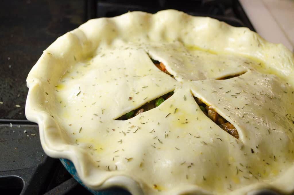 A pie crust brushed with beaten egg and cut with slits in the center is seasoned with salt, pepper and herbs.