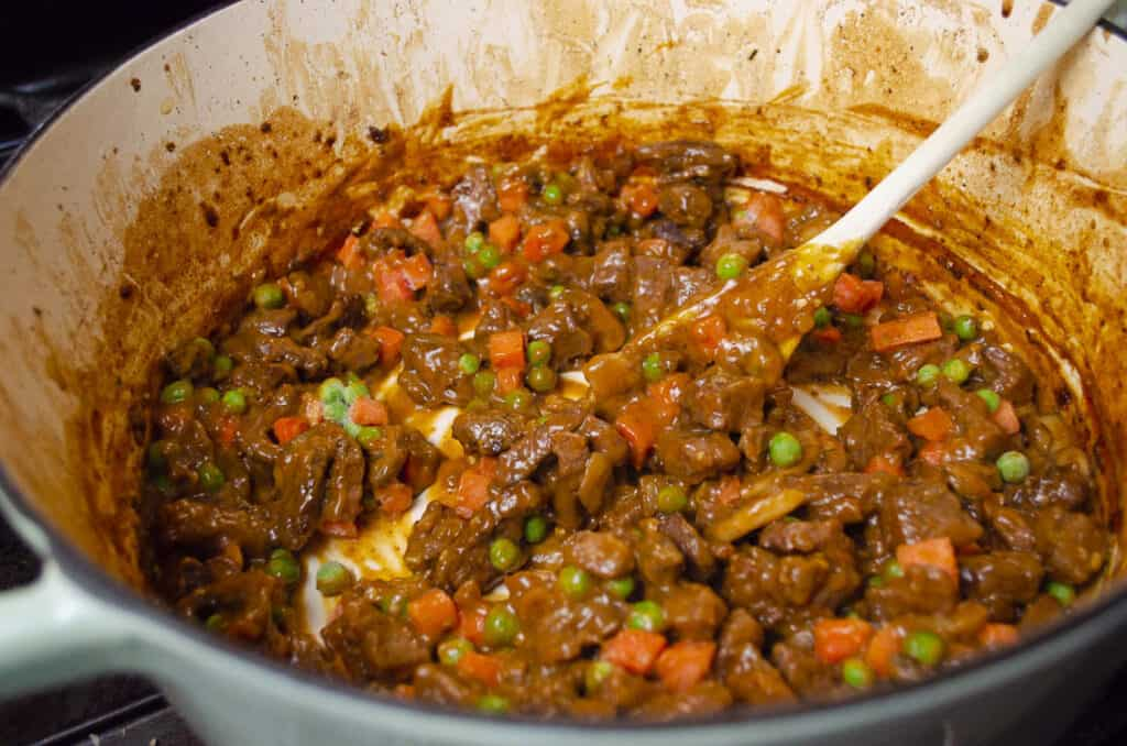 Chopped carrots and peas are stirred into Savory Beef Pot Pie filling in an enamel Dutch oven.