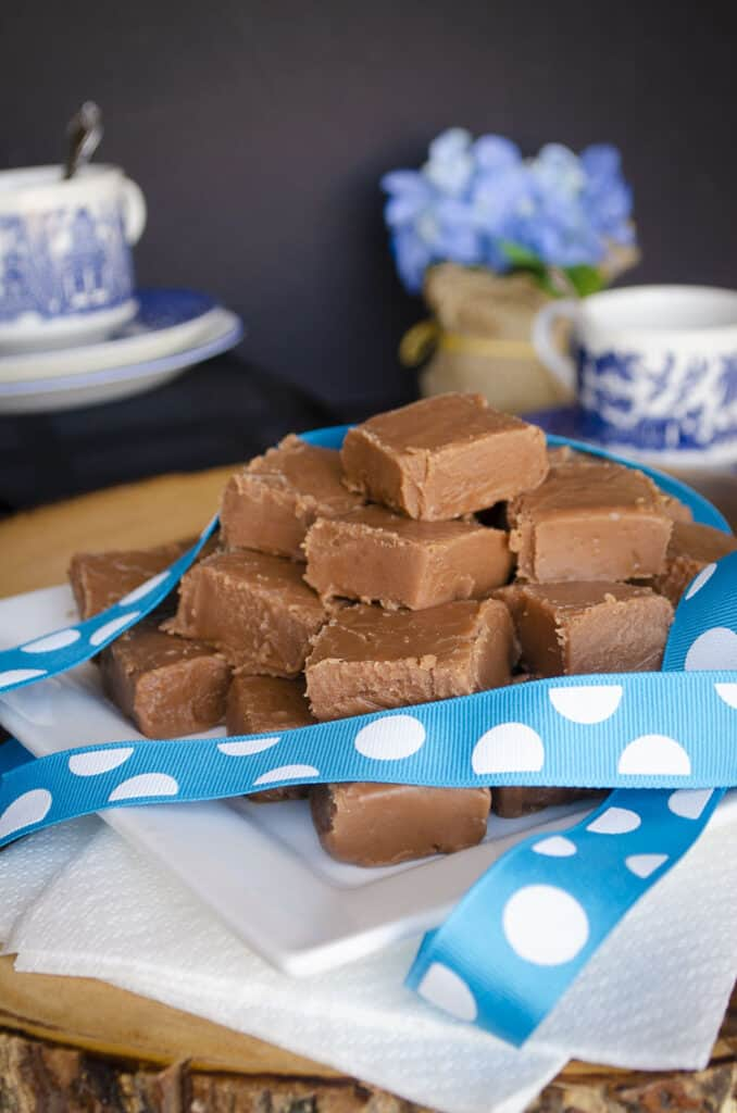 Blue-Ribbon Fudge squares sit on a white square plate with China tea cups and blue flowers in the background.