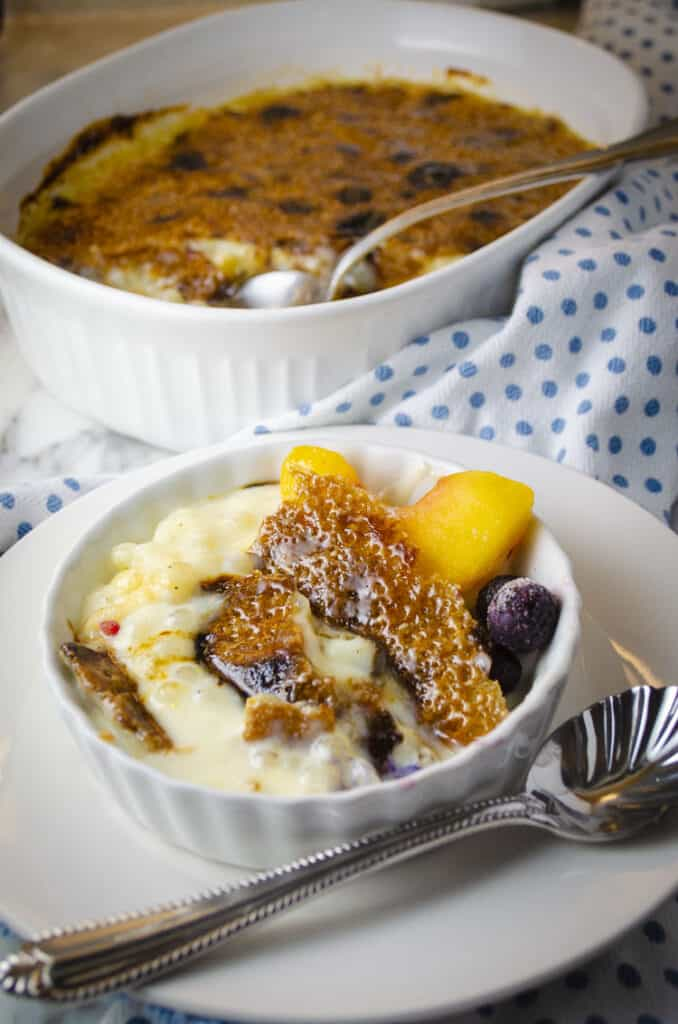 A white ceramic serving dish with Tapioca Pudding Brûlée in it, garnished with a peach slice and some blueberries. A Large baking dish with Tapioca Pudding Brûlée sits behind it in the background.