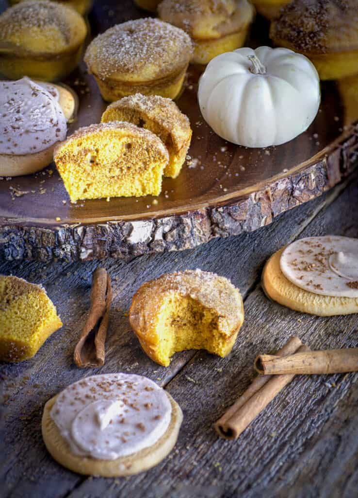 Snickerdoodle Pumpkin Muffins on a barn wood table surrounded by Snickerdoodle cookies, pumpkins and cinnamon sticks.