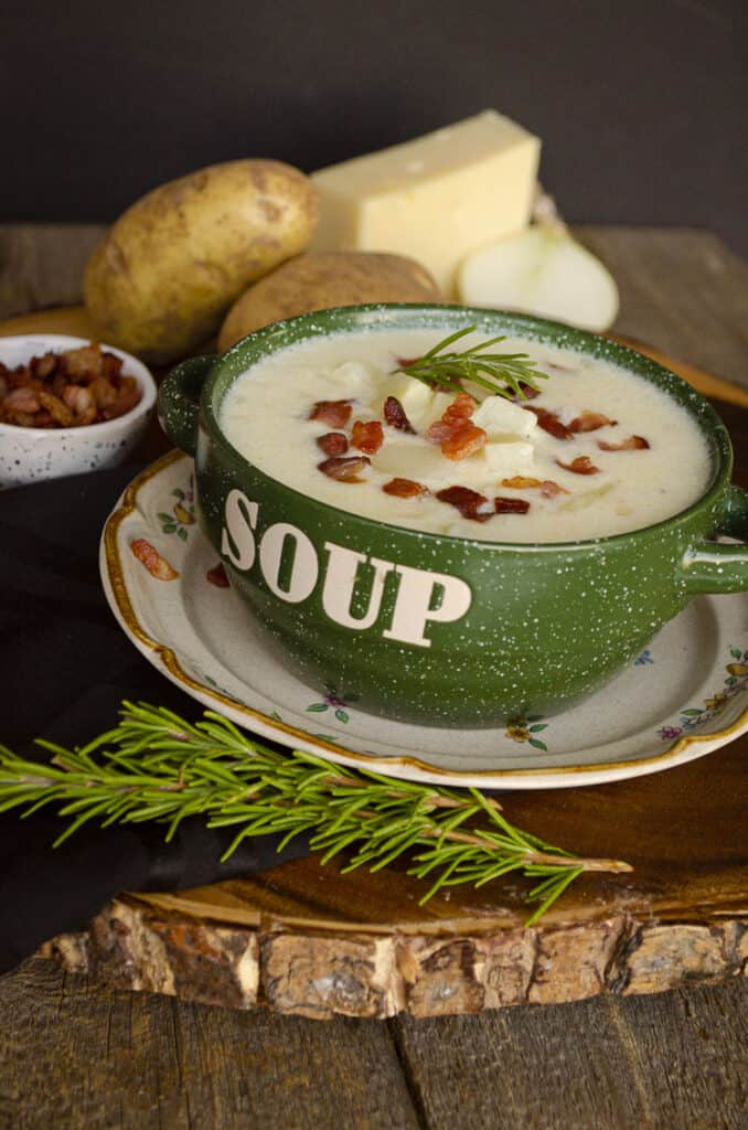 """Looing at a green bowl with the word """"soup"""" on it's side, filled with Gluten-free Swiss Potato Soup and surrounded by ingredients such as swiss cheese, raw potatoes and onion."""