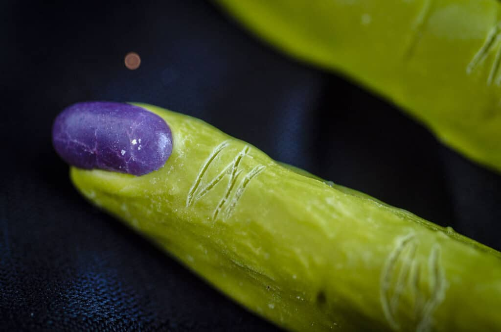 A closeup of a purple jelly bean 'finger nail' pressed into the candy melt-coated pretzel rod with lines drawn into the candy melt to look like knuckles.