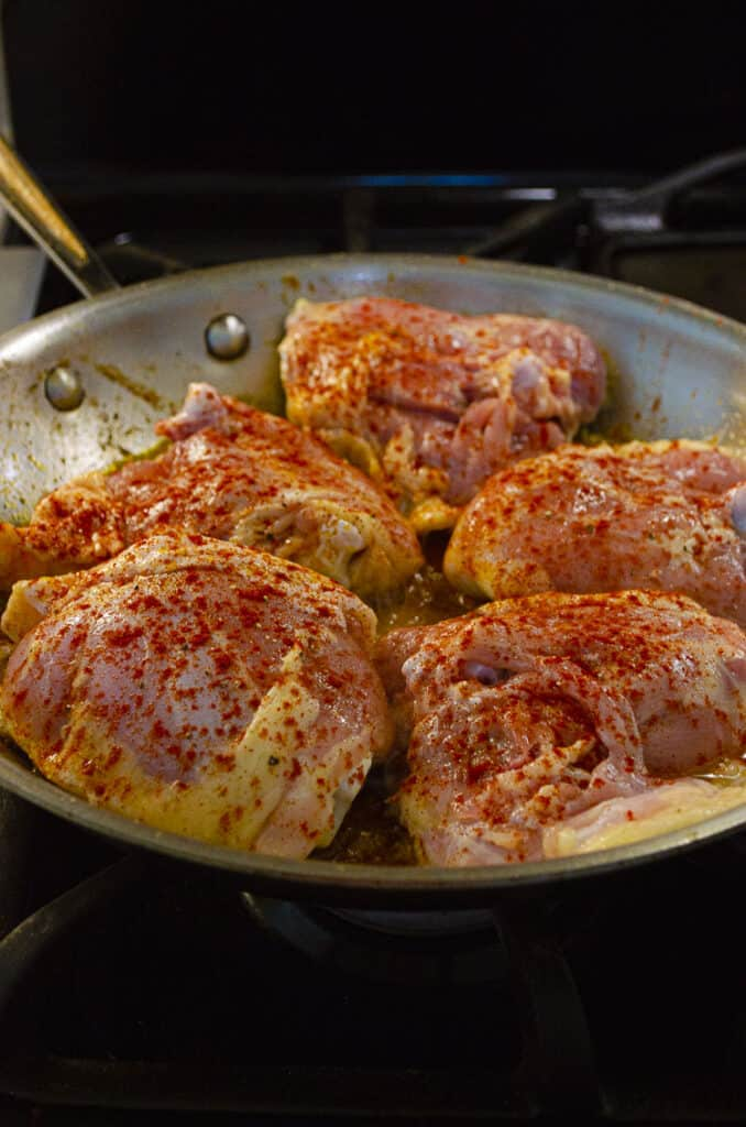 Bone-in, skin-on chicken thighs seasoned with paprika cook in a skillet.