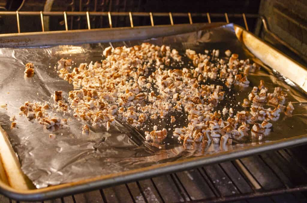 Chopped pecans in a rimmed baking sheet being toasted in an oven.