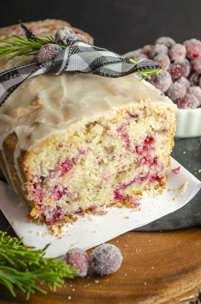 A loaf of Frosted Cranberry Nut Bread sliced open revealing it's colorful interior.