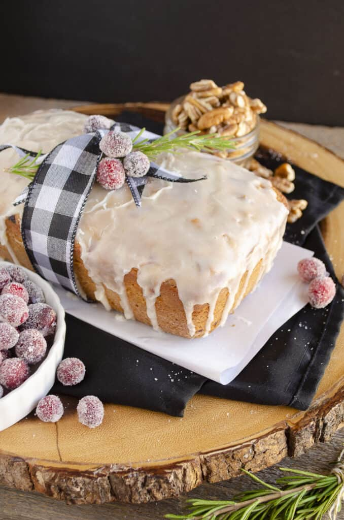 A loaf of Frosted Cranberry Nut Bread. tied with a ribbon sits on a wooden table.