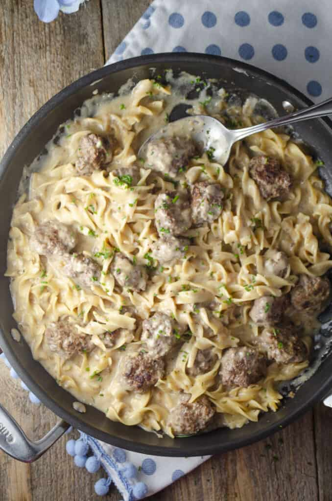 Looking down on a skillet full of 30-minute One-Pot Meatball Stroganoff (Meatballs and noodles in sauce).