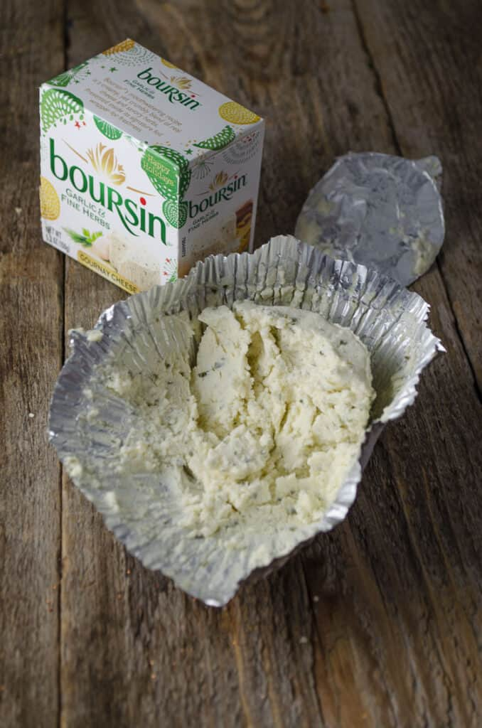 A box of Boursin Cheese with it's contents sitting opened next to it.