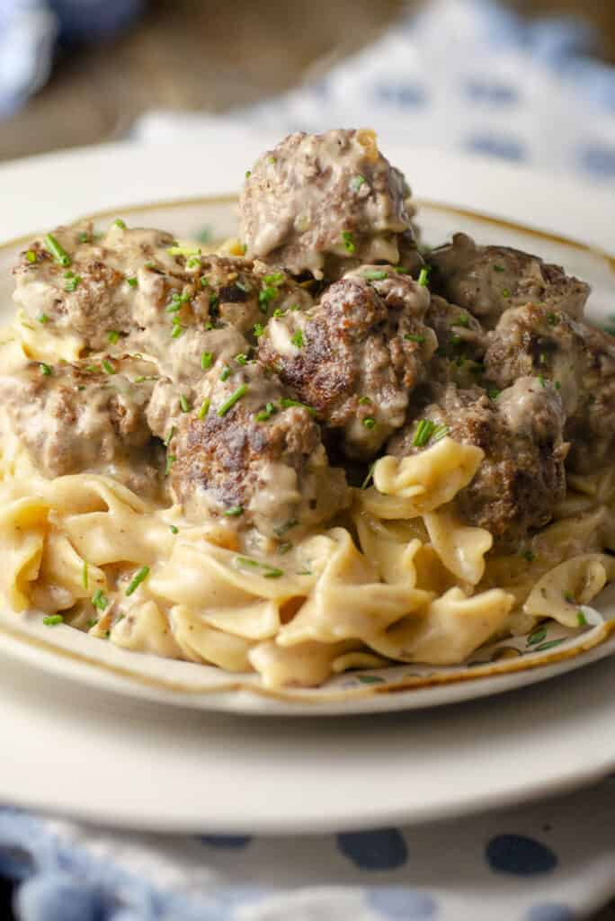 A close-up picture of a 30-minute One-Pot Meatball Stroganoff serving on a plate showing the texture and minced chives sprinkled on top.