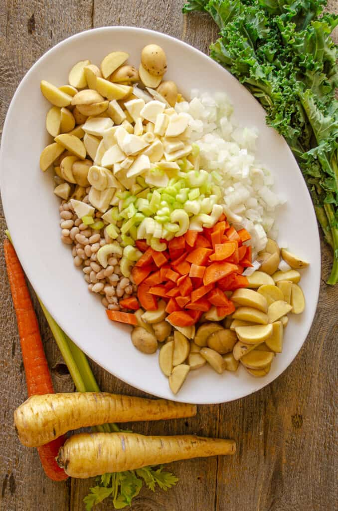 A large white oval platter on a barn wood table is filled with chopped raw vegetables for making Winter Slow-Cooker Vegetable Bacon Soup.