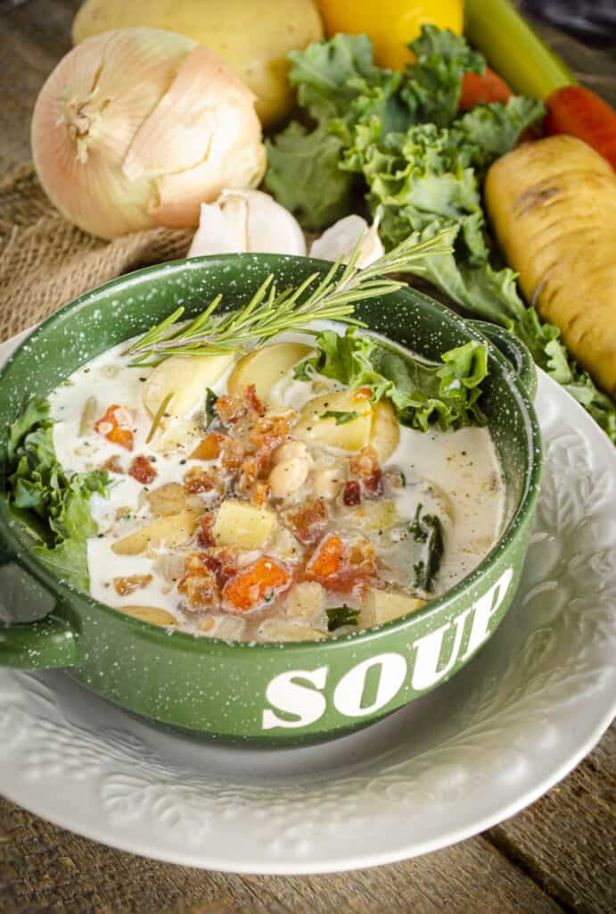 A green bowl surrounded by vegetables   is filled with Winter Slow-Cooker Vegetable Bacon Soup and garnished with a sprig of fresh rosemary.