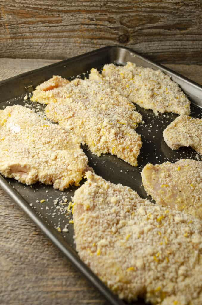 Fresh Sweet Lemon Chicken Piccata cutlets laid out flat on a rimmed baking sheet waiting to be fried.