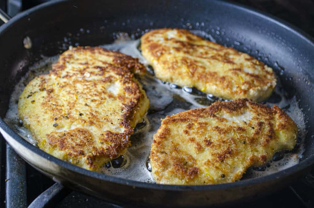 Sweet Lemon Chicken Piccata cutlets frying in caper-infused butter.