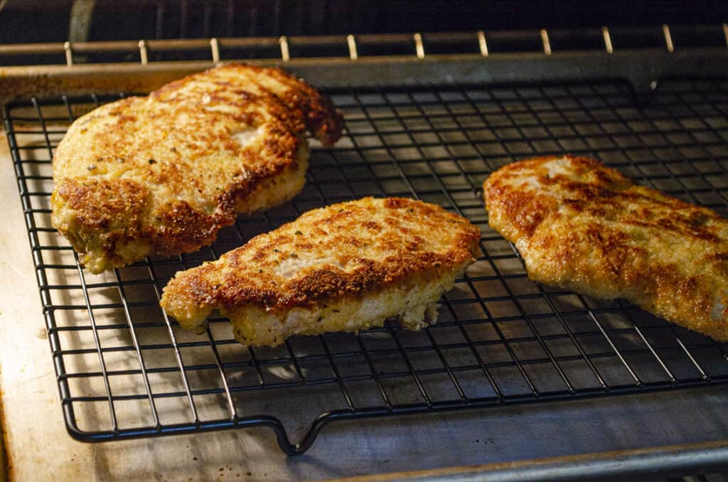 Just fried Sweet Lemon Chicken Piccata cutlets staying warm in an oven on a wire rack.
