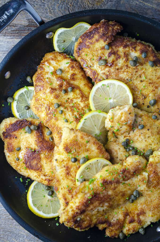 Sweet Lemon Chicken Piccata cutlets arranged with thinly sliced lemon rounds and capers, all drizzled in a sweet lemon-butter-caper pan sauce.