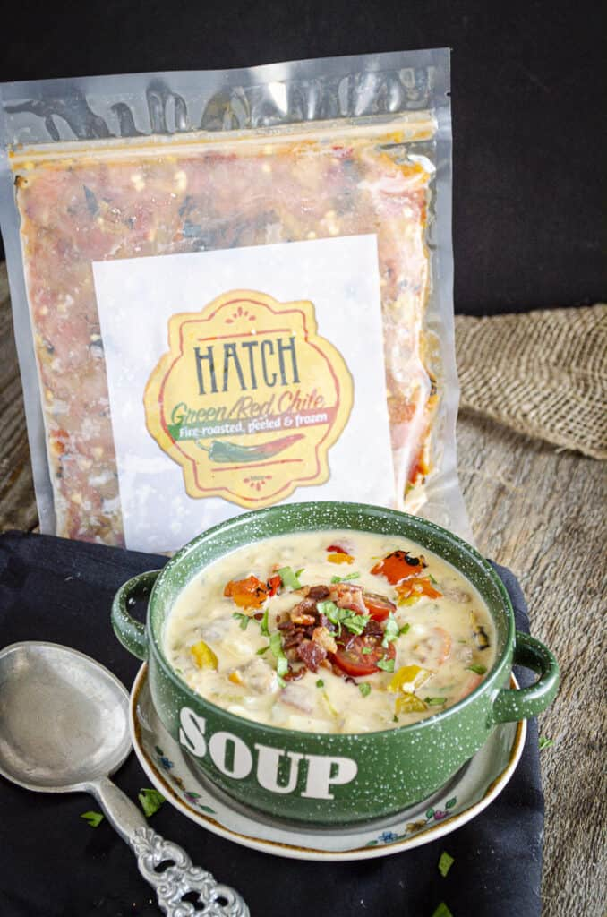 A package of chopped Hatch Green Chile sits next to a bowl of bacon cheeseburger soup sprinkled with fresh herb and sliced tomato.
